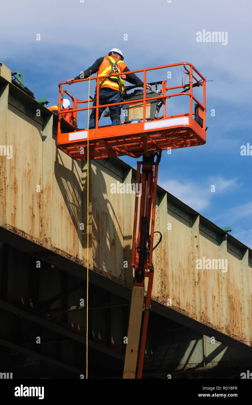 Infrastructure maintenance worker with safety harness working on a