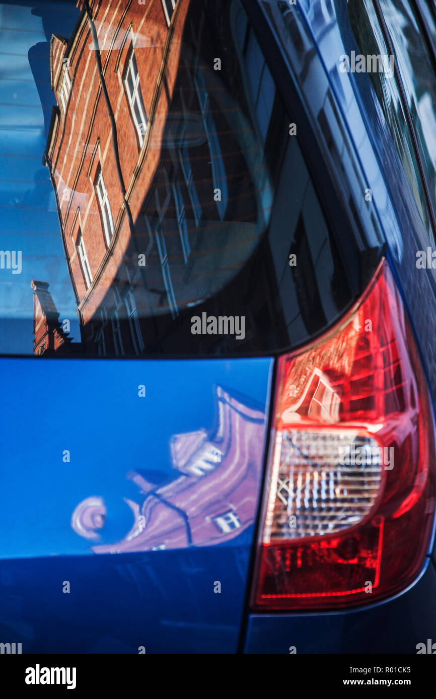 victorian red brick building distorted reflection in rear of car Stock Photo