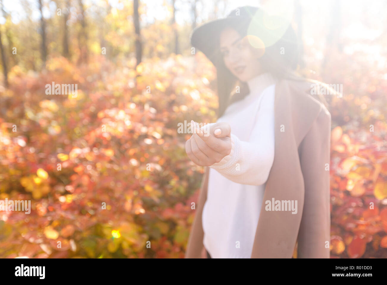 woman smiling and inviting to follow her in autumn park. - Stock Image