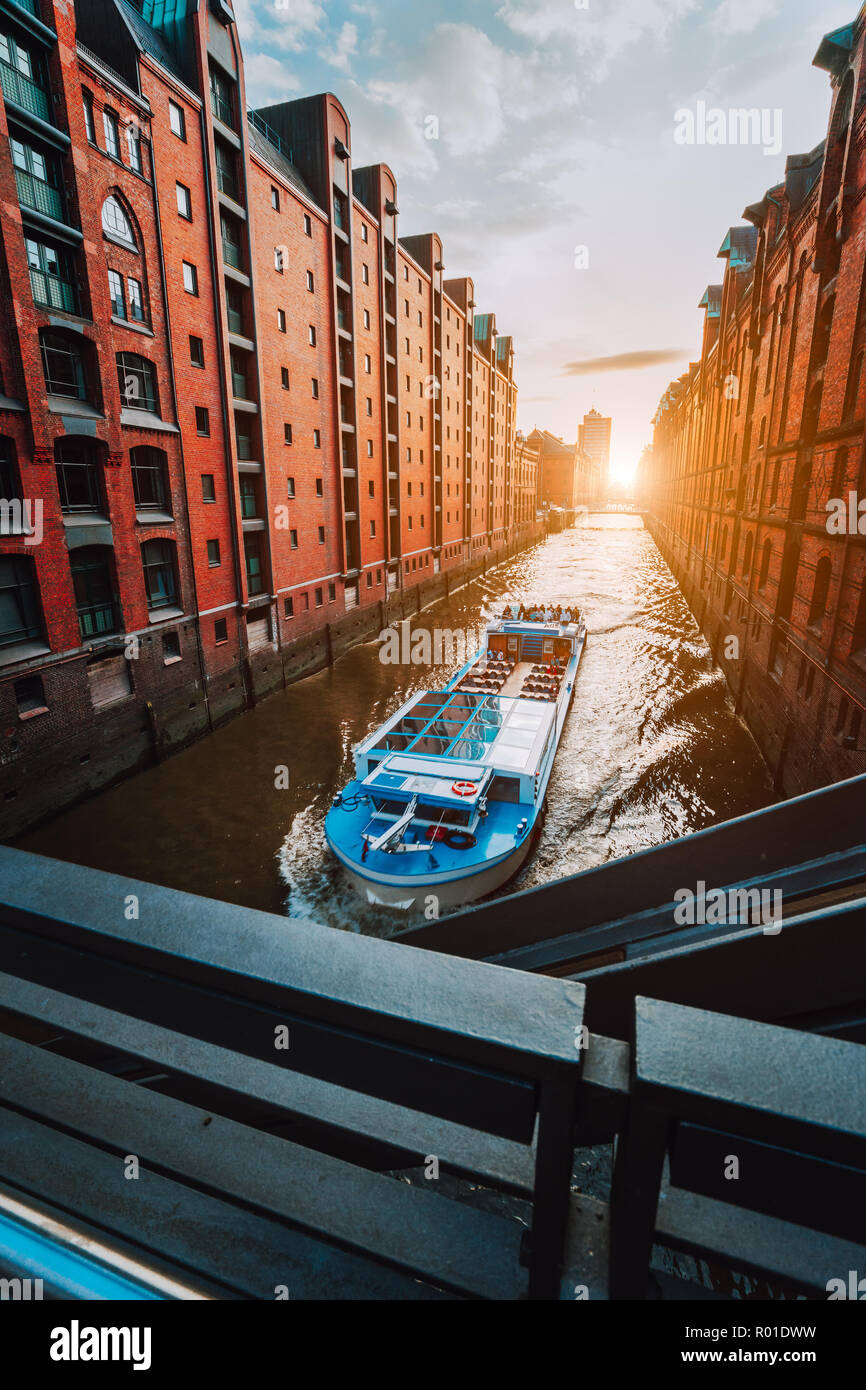 Touristic cruise boat in narrow canal of famous Speicherstadt warehouse district with red brick buildings in Hamburg, Germany - Stock Image