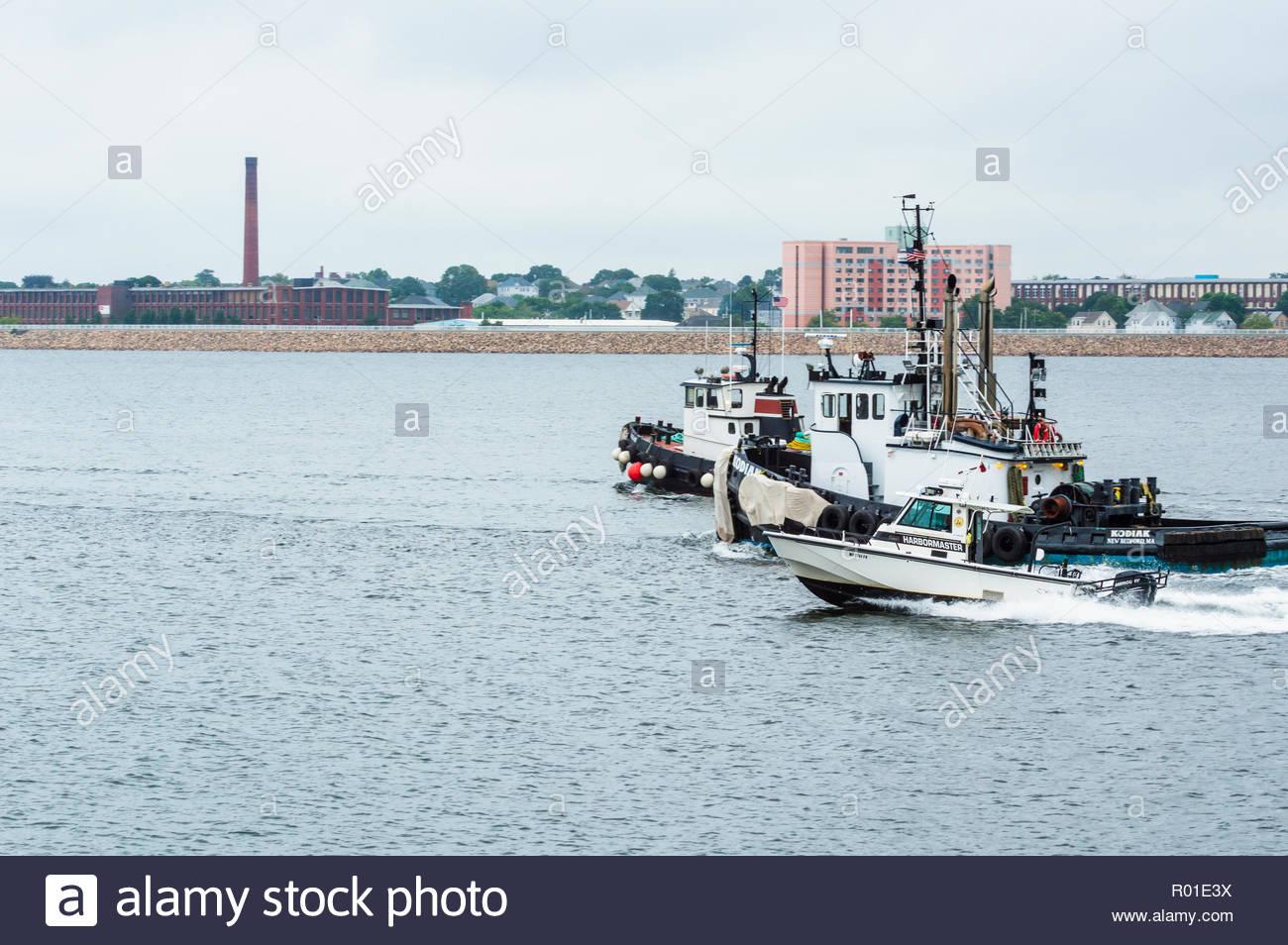 New Bedford, Massachusetts, USA - August 15, 2018: Fairhaven harbormaster's patrol boat accelerating past tugs Jaguar and Kodiak - Stock Image