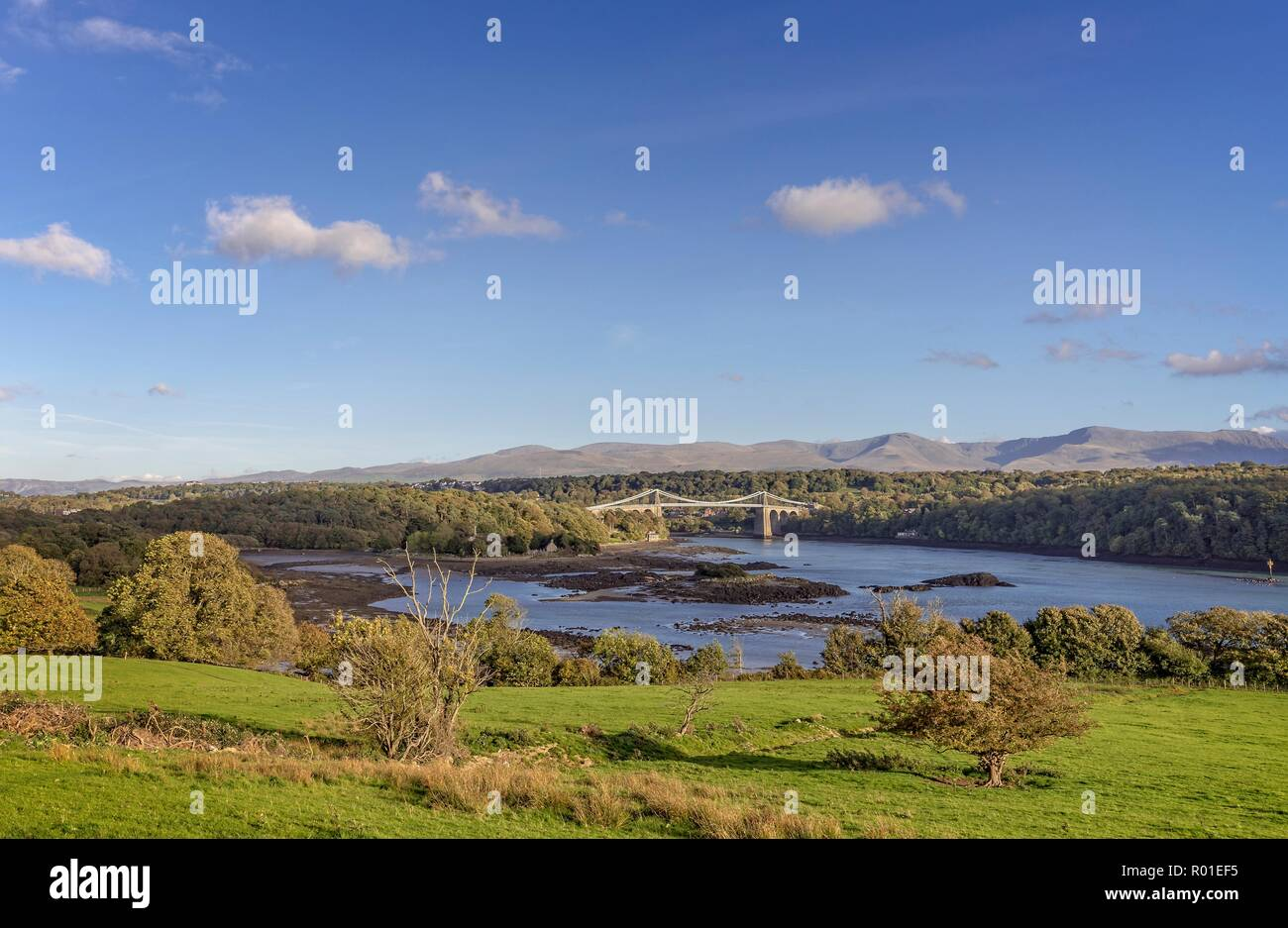 Classic view of the Menai Straits with the Menai Suspension Bridge.  The mountains of Snowdonia are in clear view in the distance. Stock Photo