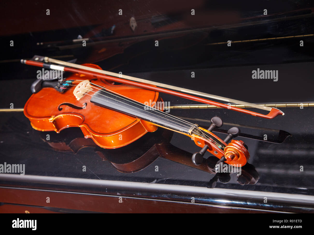 brown vintage violin with bow lying on a piano closeup indoor Stock Photo