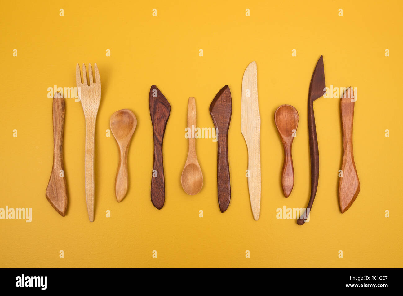 Handcrafted wooden utensils on yellow background. Fork, spoons and knives. - Stock Image