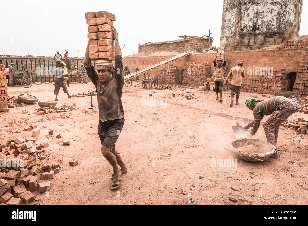 Workers with bricks on their heads in the brickyard, Dhaka, Bangladesh - Stock Image