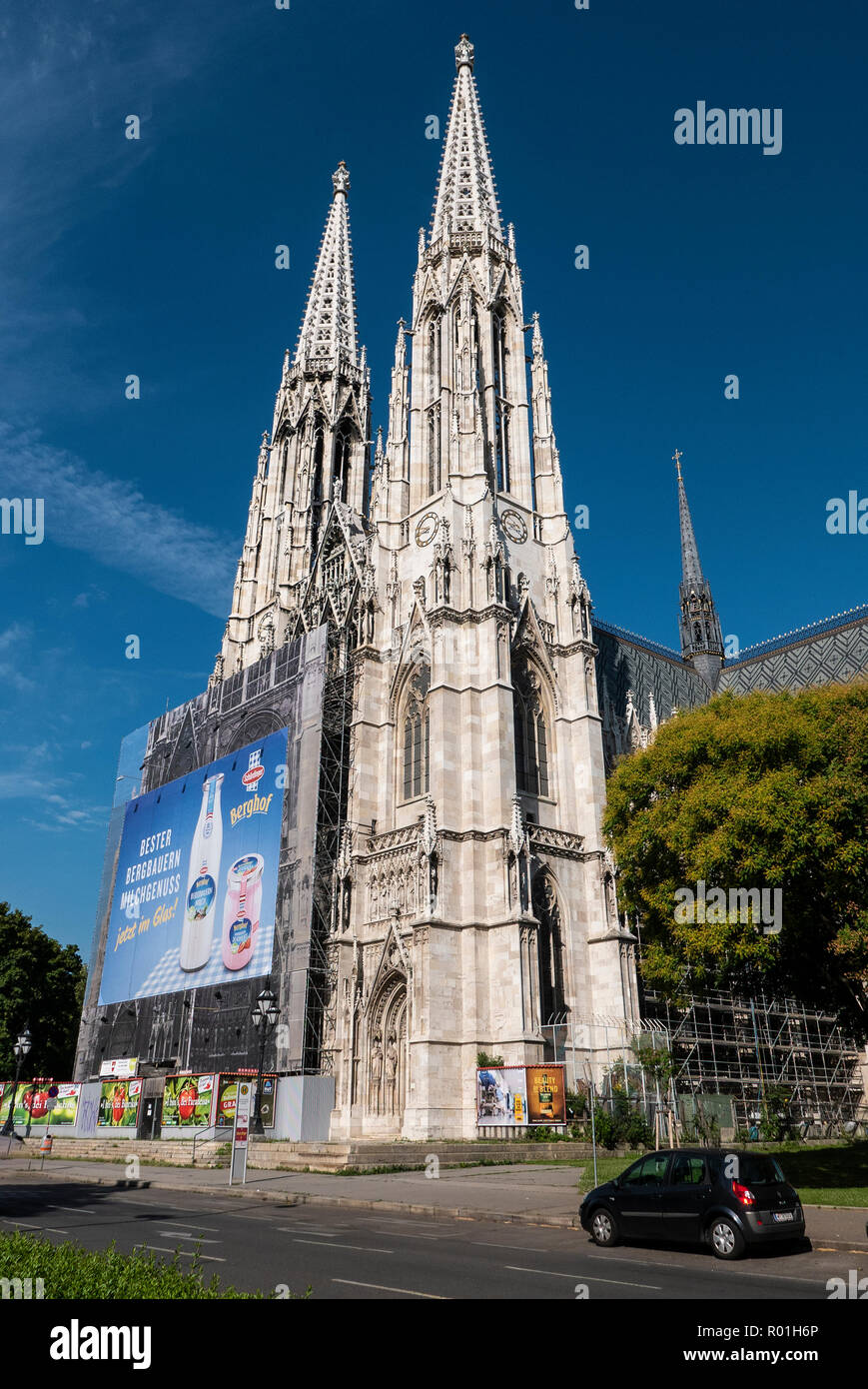 Votivkirche in Vienna turned billboard, an eyesore that lessens the city's readability and reveals dysfunctional local authorities. How dare they? - Stock Image
