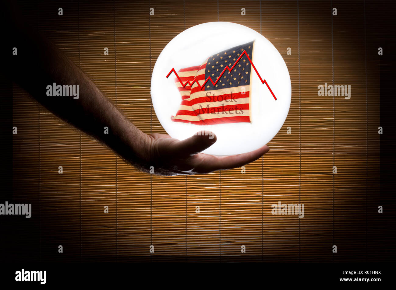Human Hand Holding a Crystal Ball predicting the American Stock Market - Stock Image