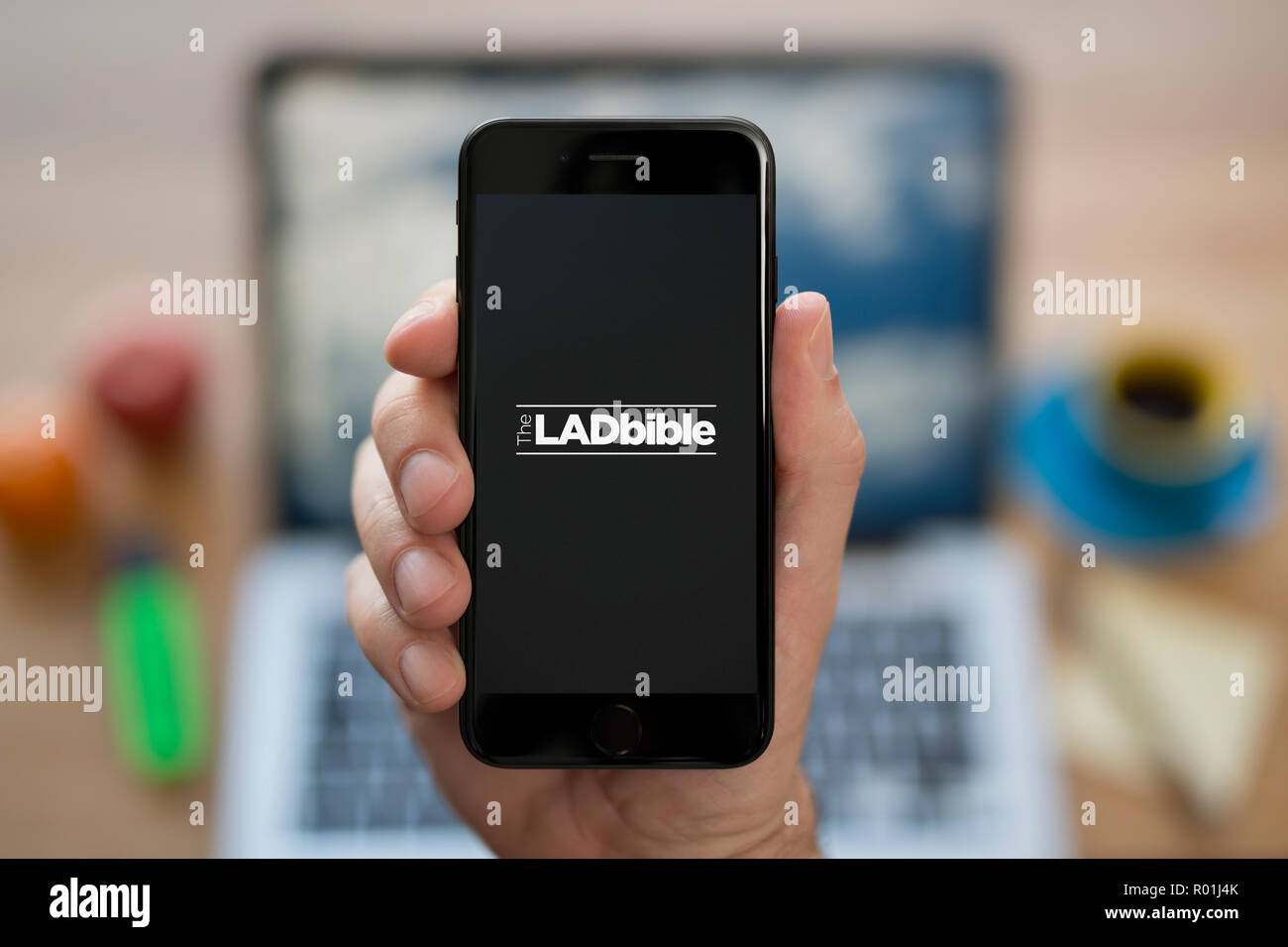 A man looks at his iPhone which displays the Lad bible logo, while sat at his computer desk (Editorial use only). Stock Photo