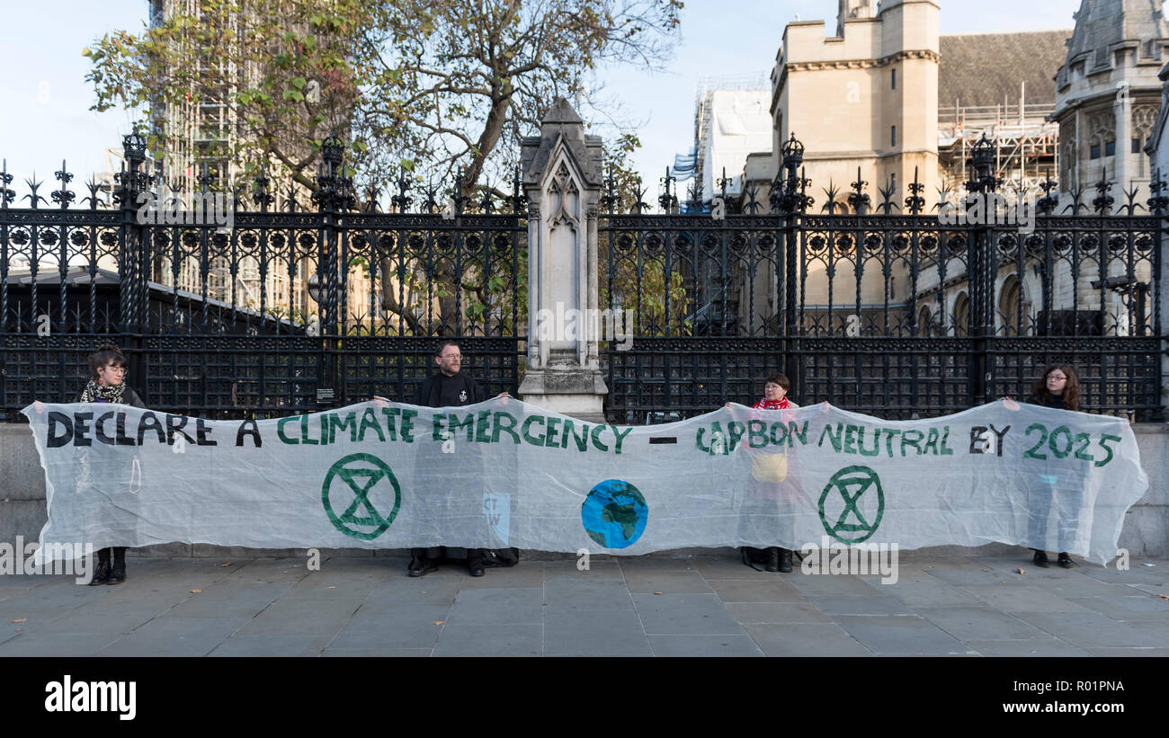 London, UK.  31 October 2018.  Activists from a group called Extinction Rebellion hold up a banner outside the Houses of Parliament.  The group is campaigning for increased government action to combat climate change and other environmental problems.  Credit: Stephen Chung / Alamy Live News - Stock Image