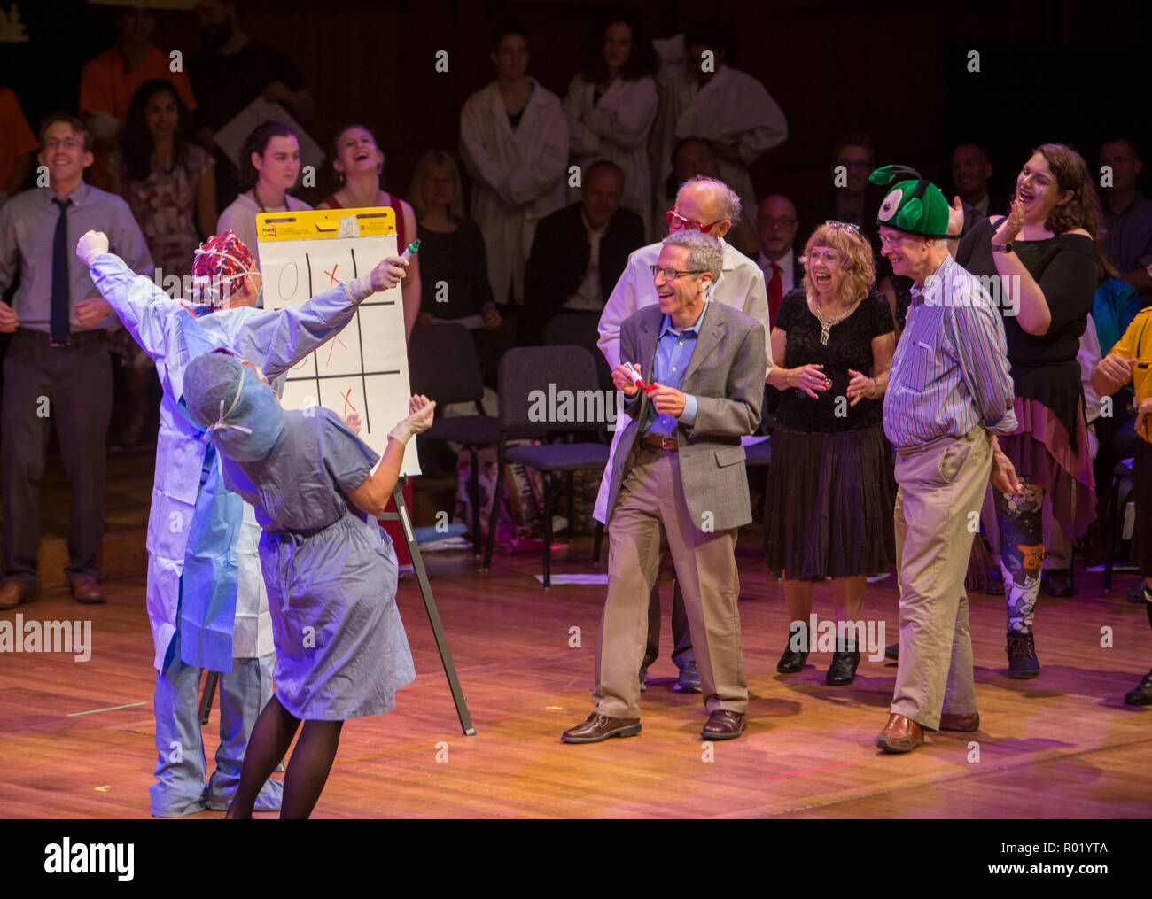 "September 23, 2016 Harvard University, Cambridge, Massachusetts, United States: Nobel laureates Rich Roberts (green Hat) and Eric Maskin (holding a marker) and Dudley Herschbach (behind Maskin), compete in a game of ""tic-toc-toe"" with a brain surgeon during the 26th First Annual Ig Nobel Prize ceremony at Sanders Theatre, Memorial Hall, Harvard University. Stock Photo"