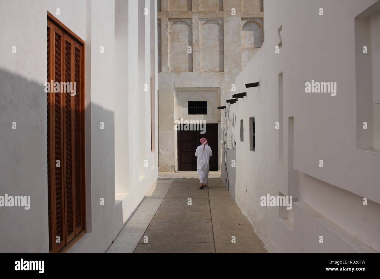 A Bahraini man wearing dishdash, guthra, and aghal walking along a narrow alley on the Pearl Trail, old Muharraq, Kingdom of Bahrain - Stock Image
