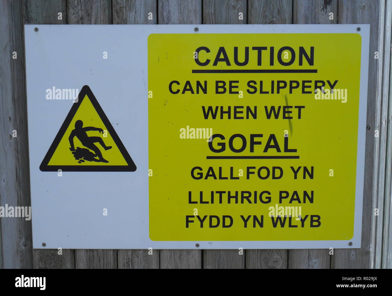 Sign in English and Welsh warning of a slippery floor, Cardiff Bay, Cardiff, South Wales, United Kingdom - Stock Image