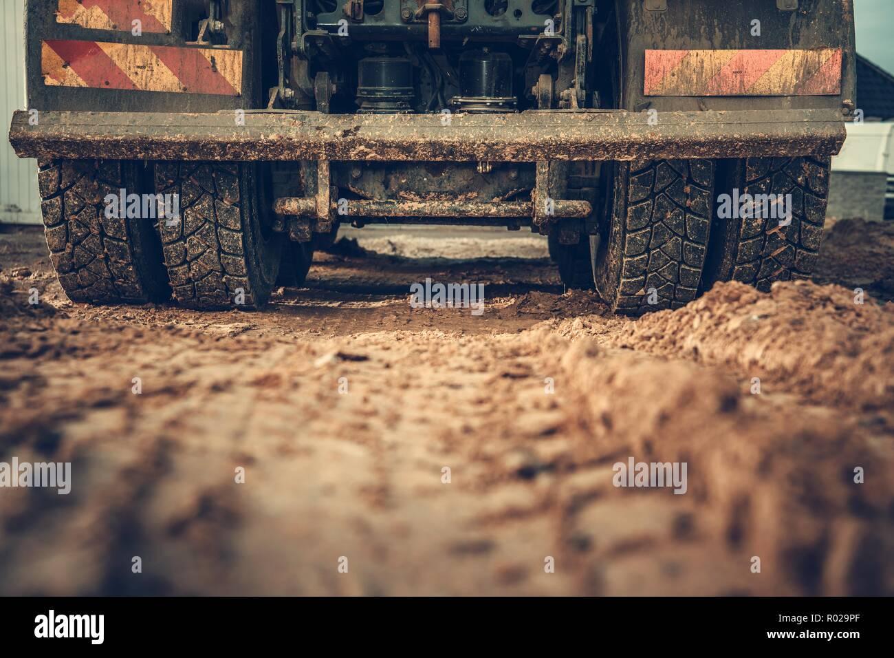 Dump Truck Ground Works Closeup Photo. Heavy Duty Vehicle Rear Wheels Closeup. Construction Site. - Stock Image