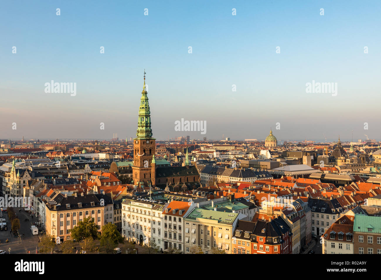 Copenhagen skyline in evening light. Copenhagen old town and copper spiel of Nikolaj Church. City streets and danish house roofs. High angle view from - Stock Image