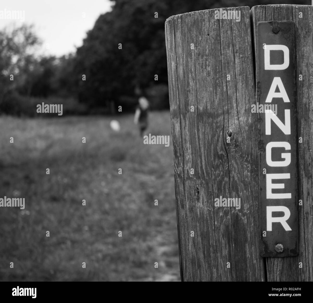 Metal danger sign on wooden gate post with blurred figure in background - Stock Image