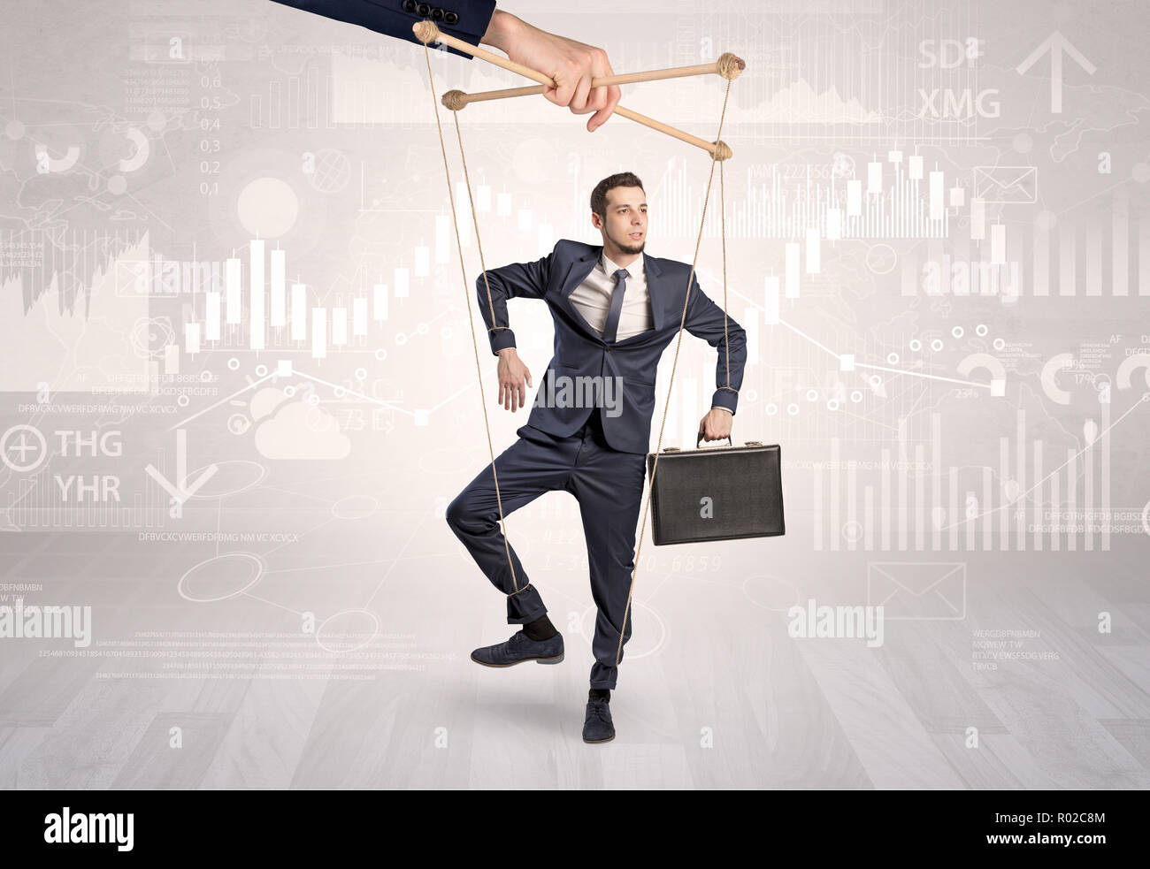 Puppet businessman controlled by another hand with financial concept  - Stock Image