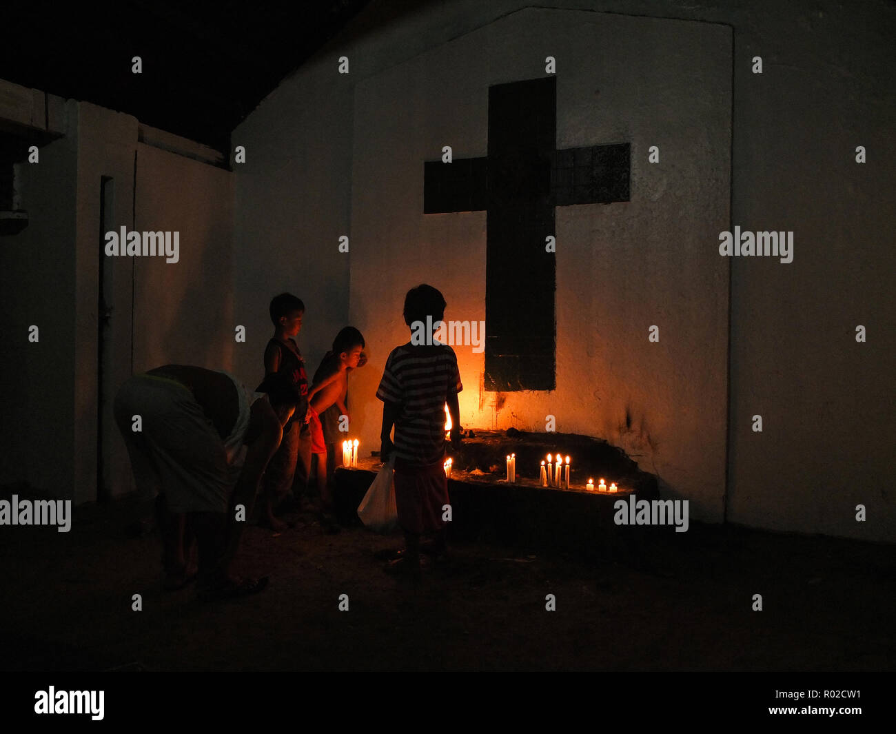 Street kids are seen gathered next to candle waxes at the makeshift altar, for those people who cannot visit their relative's tomb in faraway provinces. Filipinos prepares for All Saints Day (Day of the Dead) or Todos Los Santos in Spanish term. They clean, paint the tomb of their deceased relatives on the eve of the celebration. - Stock Image
