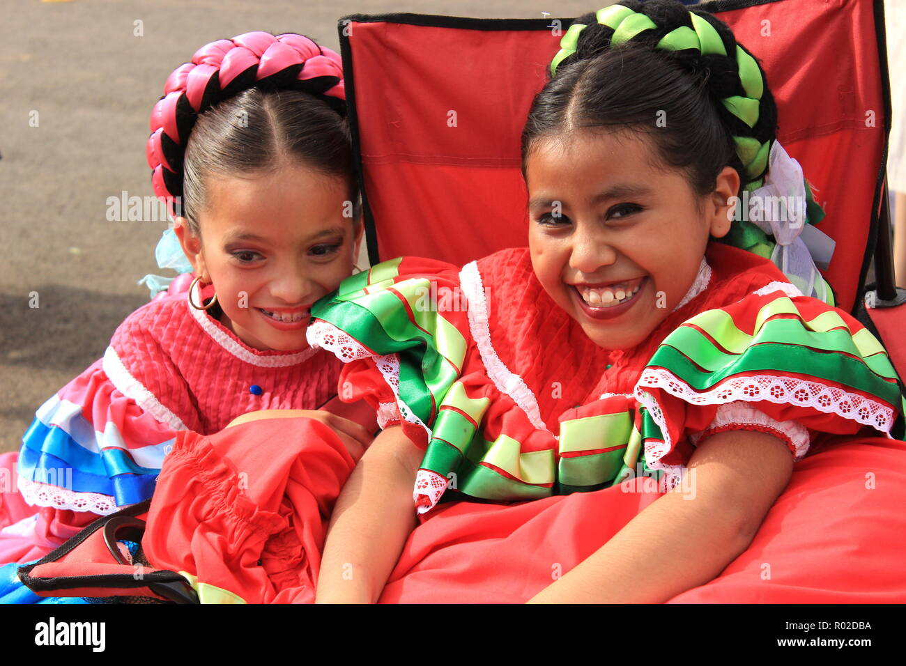 40de04bcfec Young girls in traditional Mexican dresses have fun while they wait for  their performance