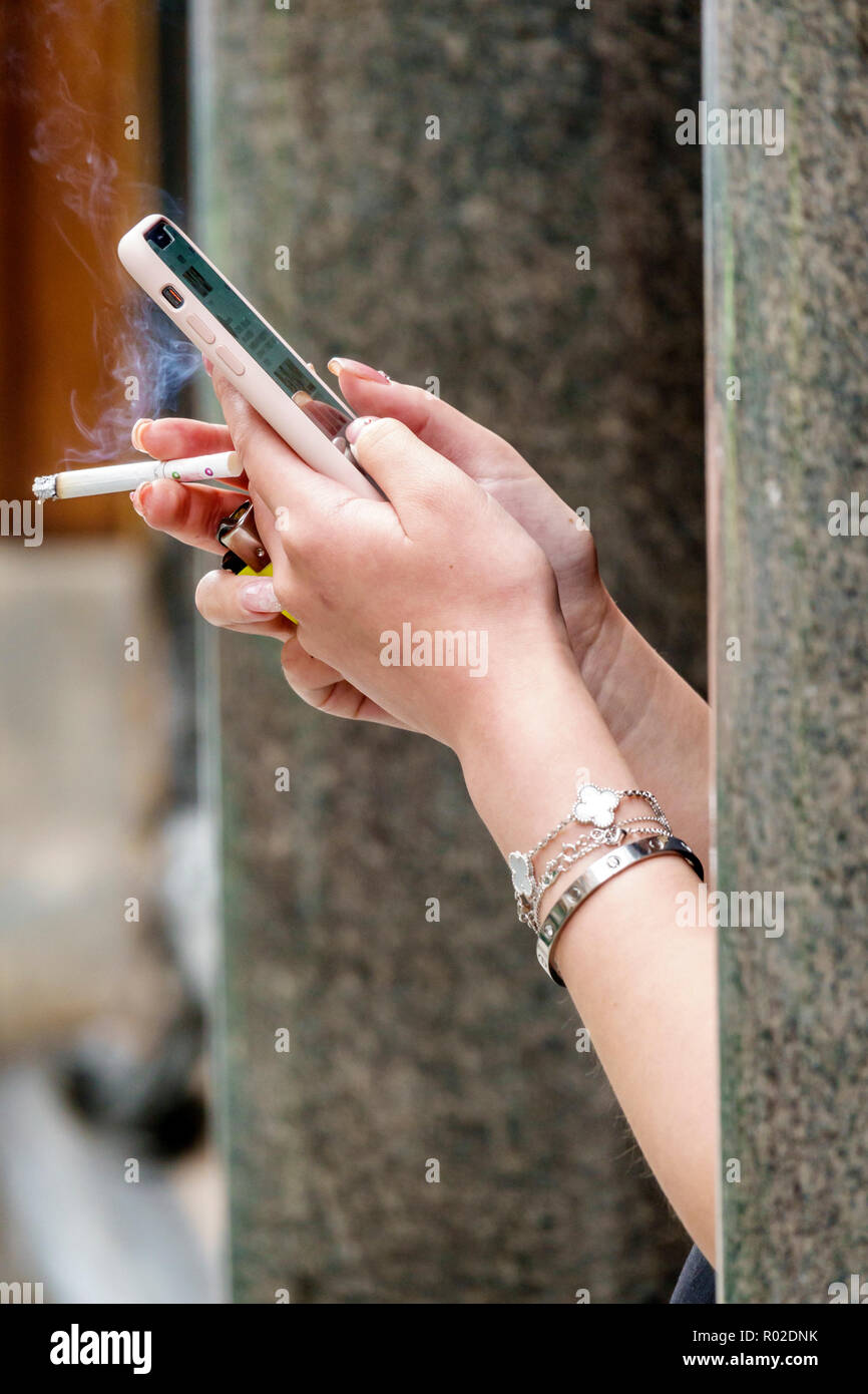 London England United Kingdom Great Britain Mayfair cigarette smoking smoke outdoor sidewalk woman's hands using smartphone nicotine addiction texting - Stock Image