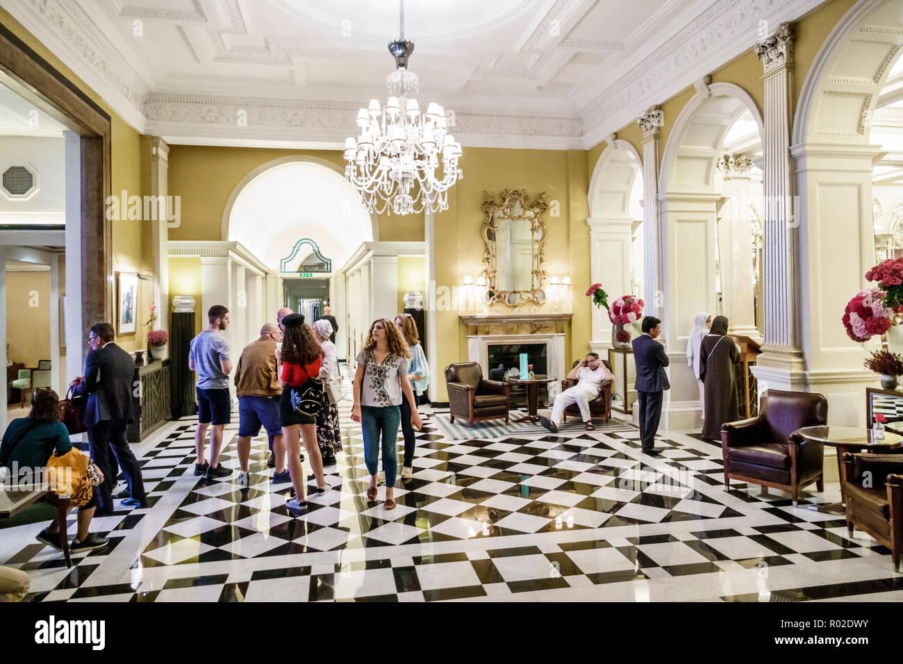 London England United Kingdom Great Britain Mayfair Claridge's hotel 5-star luxury historic building inside interior lobby chandelier black white chec - Stock Image