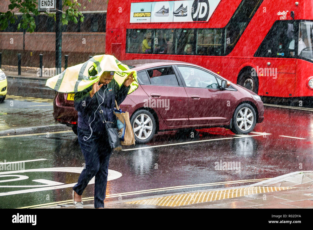 London England United Kingdom Great Britain Lambeth South Bank raining rainy weather wet pavement pedestrian crossing traffic Black woman covering hea - Stock Image
