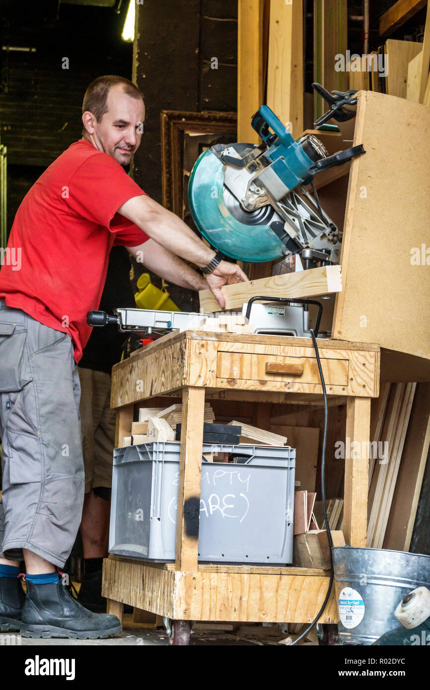 London England United Kingdom Great Britain Lambeth South Bank workshop workbench worker table saw electric tool carpenter working man - Stock Image