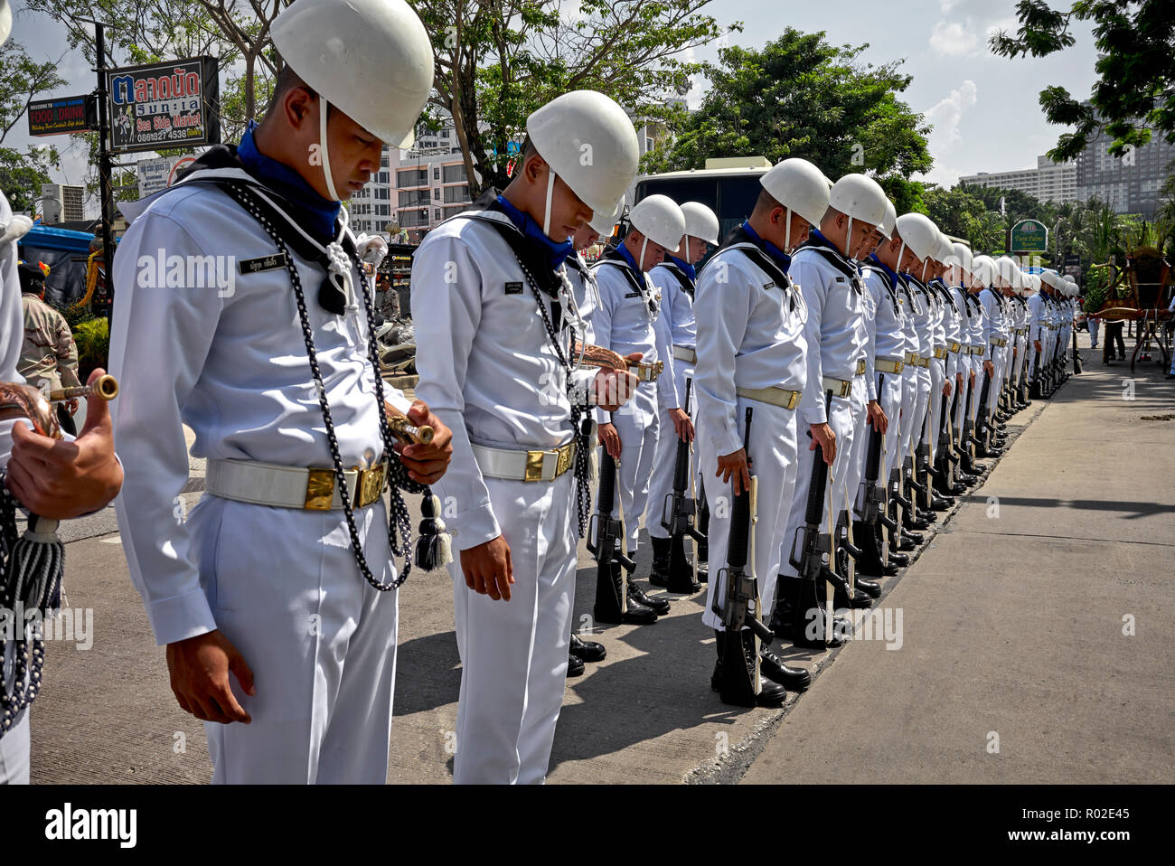 Thailand navy personnel on parade in full military whites and bowing in respect to the Thai King - Stock Image