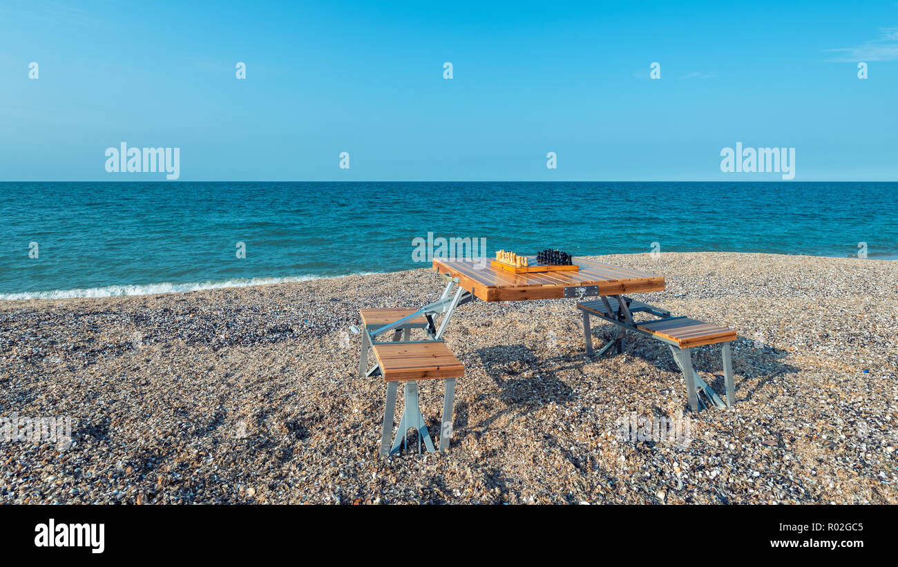 Chess board on the table by the sea - Stock Image