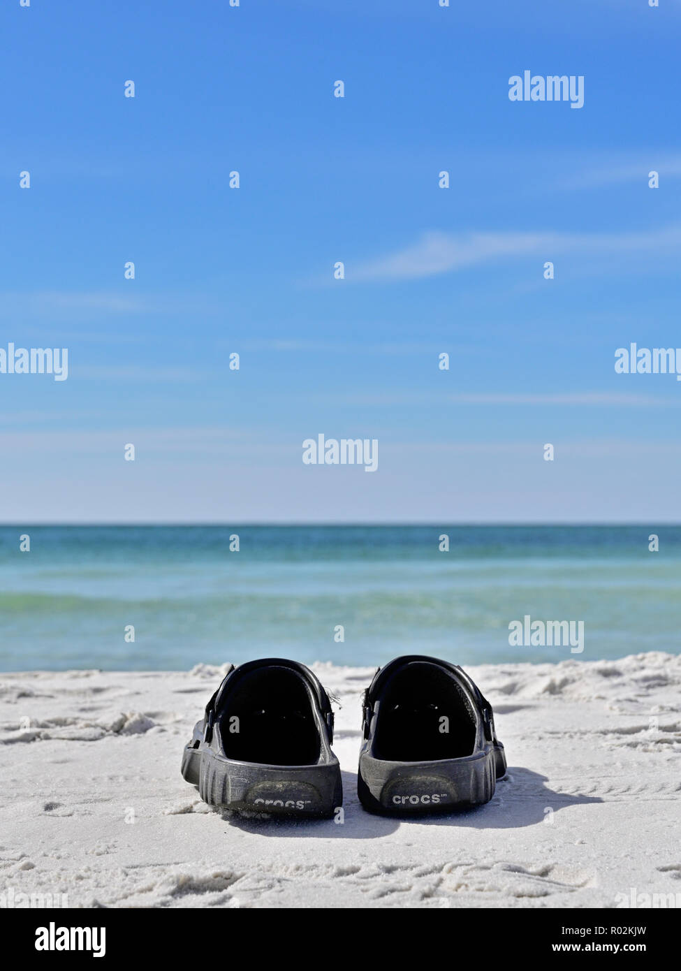 Pair of Crocks beach shoes or sandals on white Florida panhandle Gulf coast beach sand facing the Gulf of Mexico at Deer Lake State Park, Florida USA. - Stock Image