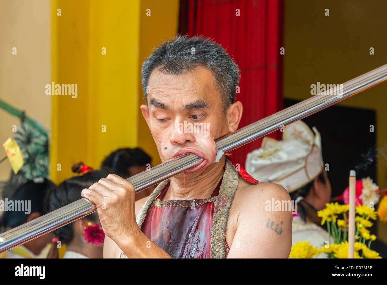 Phang Nga, Thailand - October 14, 2018: Man demonstrating sharp steel run through the mouth in vegetarian festival parade in Phang Nga, Thailand - Stock Image