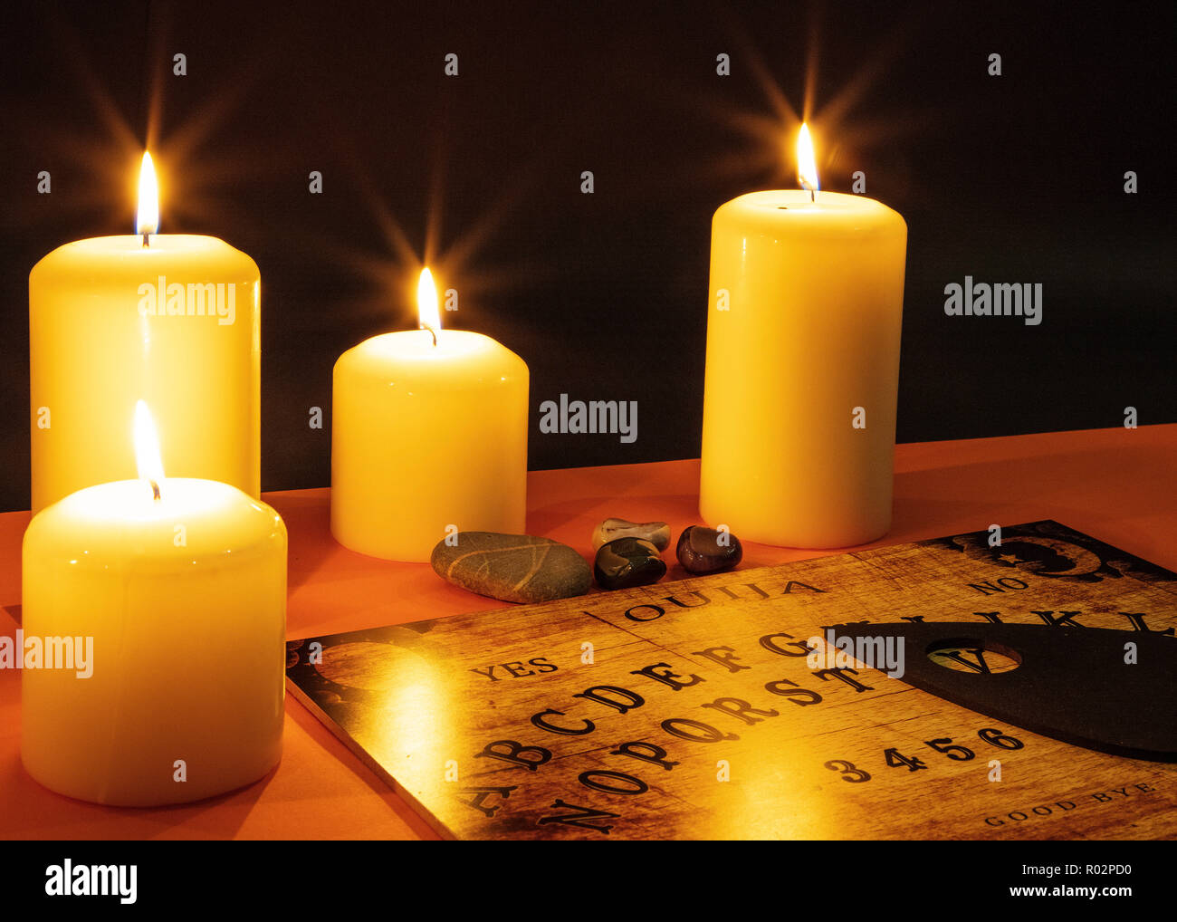 Ouija board in a darkened, candlelit scary room - Stock Image
