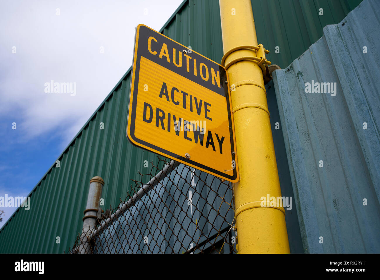 Yellow Caution, active driveway, traffic sign - Stock Image
