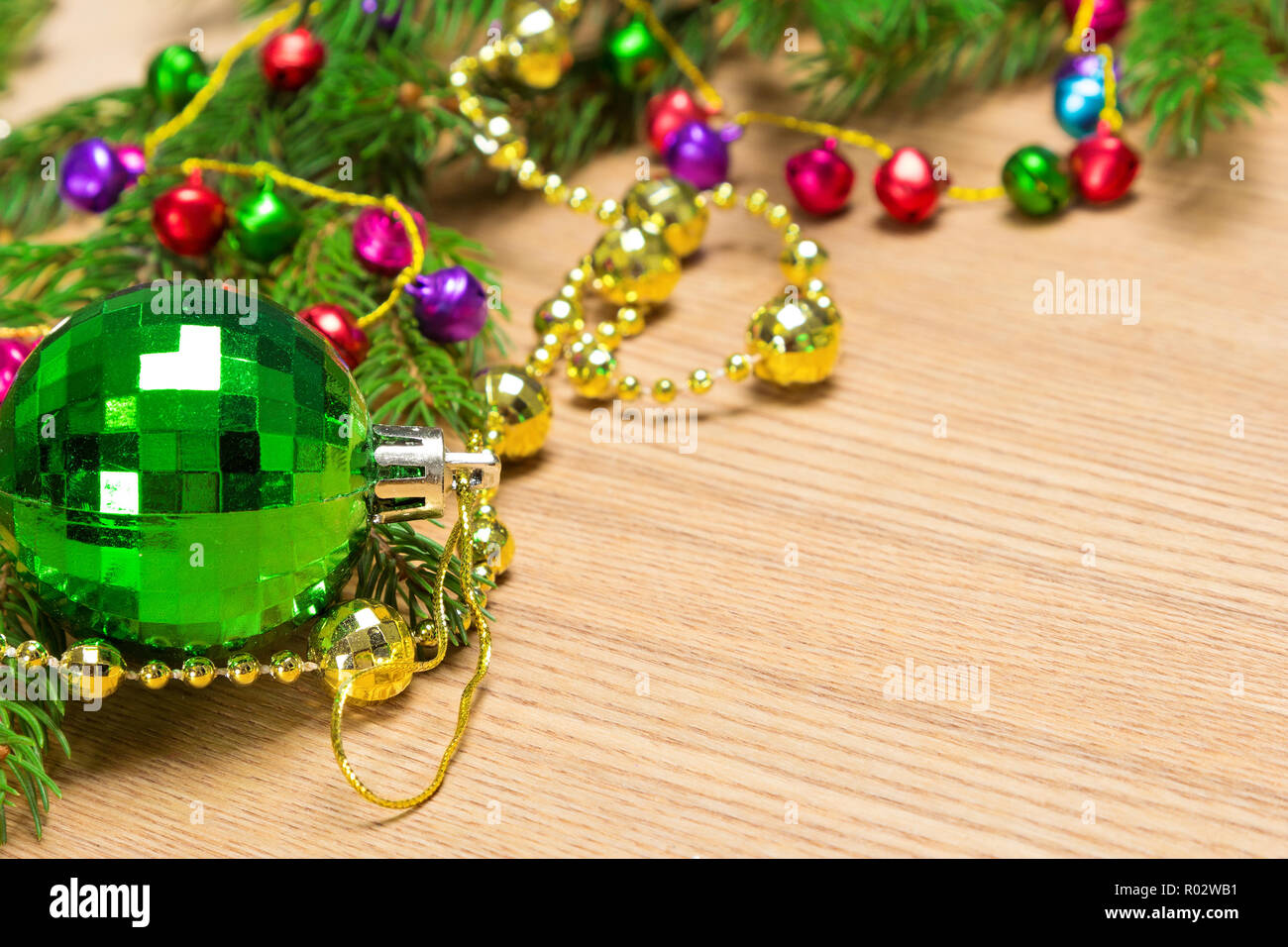 Christmas and New Year festive background. Green Christmas ball, garland of varicolored bells and beads golden color with spruce branches on wooden su - Stock Image