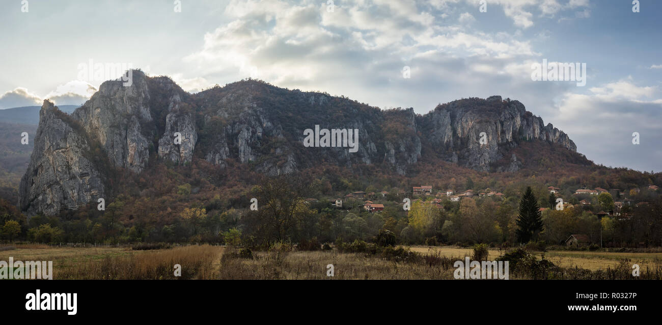 Large panorama of iconic village Vlasi at the base of a rocky mountain and at the entrance of famous Jerma River canyon - Stock Image