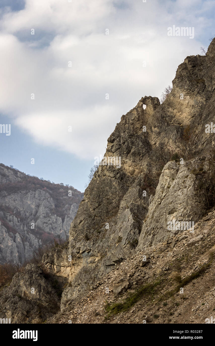 Pointy rock with a hole at the summit of a rocky mountain in the canyon of Jerma river in Serbia - Stock Image