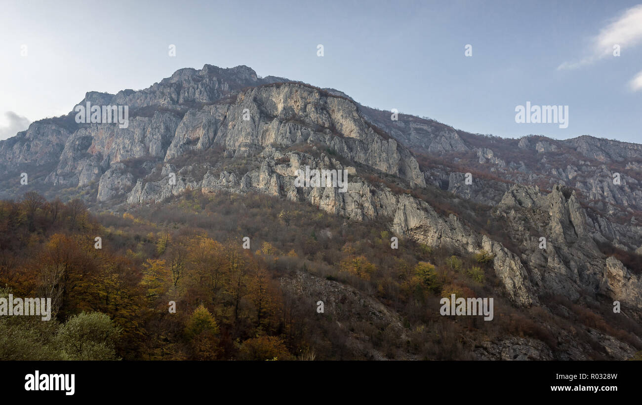 Rocky cliff, autumn colored trees and blue sky above canyon of Jerma river in Serbia - Stock Image
