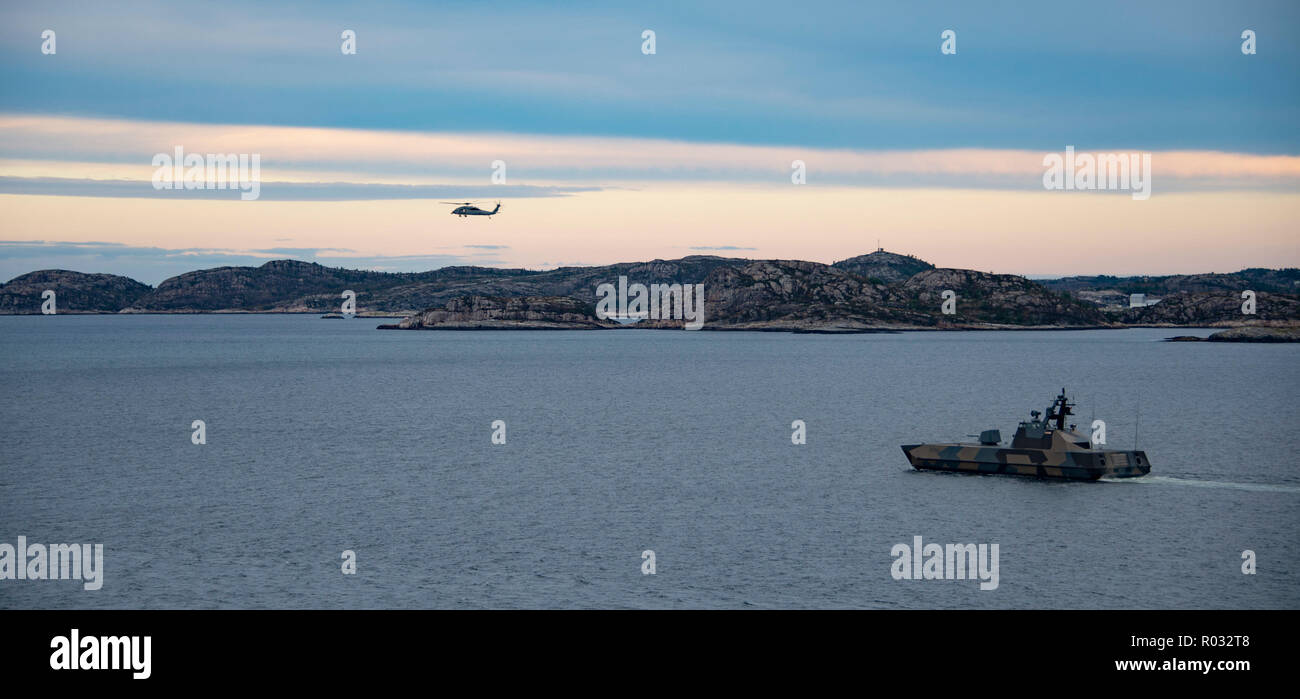 181031-N-JS726-0135    NORWEGIAN SEA (Oct. 31, 2018) An MH-60S Sea Hawk, attached to Helicopter Sea Combat Squadron (HSC) 22, conducts flight operations as the Royal Norwegian Navy Skjold-Class fast patrol boat HNOMS Storm (P961) patrols the Alvund Fjord during Trident Juncture 2018, Oct. 31, 2018. Trident Juncture 2018 is a NATO-led exercise designed to certify NATO response forces and develop interoperability among participating NATO Allies and partner nations. (U.S. Navy photo by Chief Mass Communication Specialist David Holmes/Released) Stock Photo