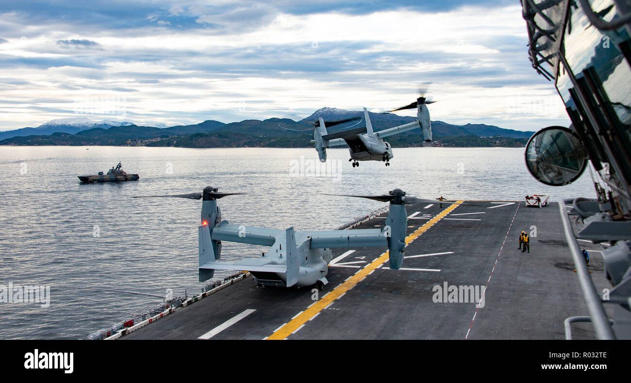 181031-N-JS726-0624    NORWEGIAN SEA (Oct. 31, 2018) An MV-22B Osprey, attached to Marine Medium Tiltrotor Squadron (VMM) 365 (Reinforced), takes off from the Wasp-class amphibious assault ship USS Iwo Jima (LHD 7) while the Royal Norwegian Navy Skjold-Class fast patrol boat HNOMS Storm (P961) patrols the Alvund Fjord during Trident Juncture 2018, Oct. 31, 2018. Trident Juncture 2018 is a NATO-led exercise designed to certify NATO response forces and develop interoperability among participating NATO Allies and partner nations. (U.S. Navy photo by Chief Mass Communication Specialist David Holme Stock Photo
