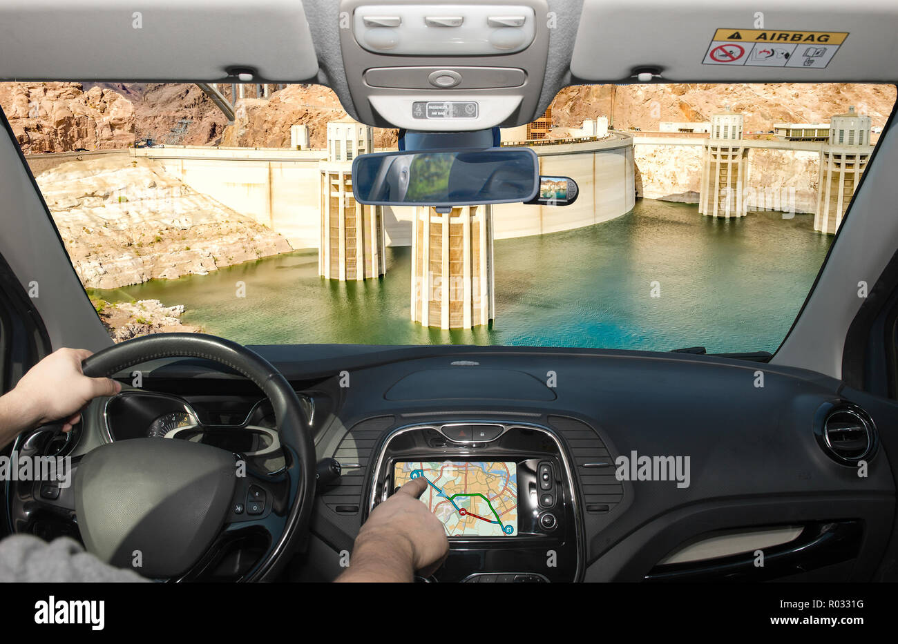 Driving a car while using the touch screen of a GPS navigation system towards Hoover Dam and Colorado River at the border between Nevada and Arizona,  - Stock Image