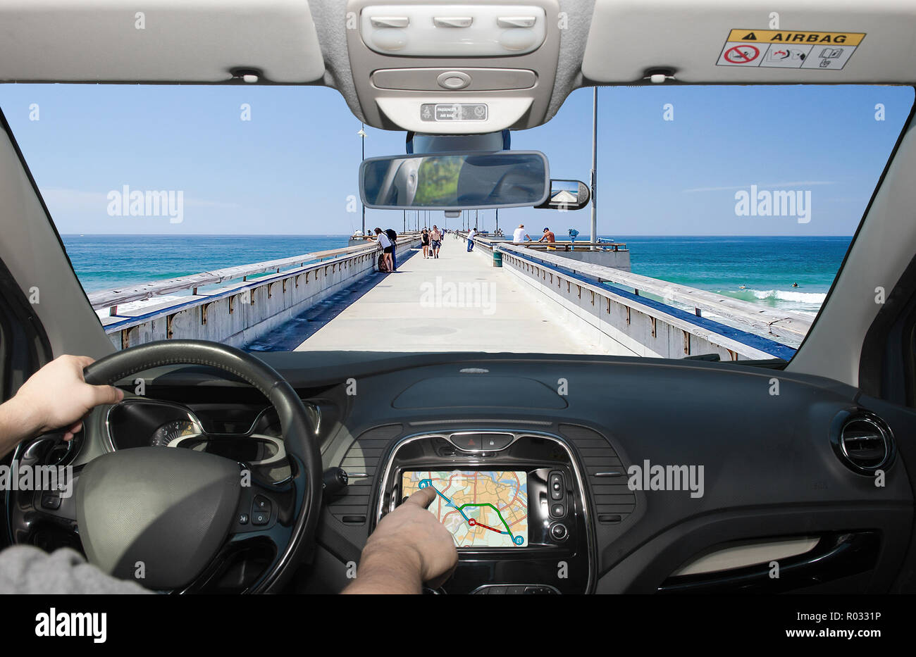 Driving a car while using the touch screen of a GPS navigation system towards Venice Beach Pier, Los Angeles, California, USA - Stock Image