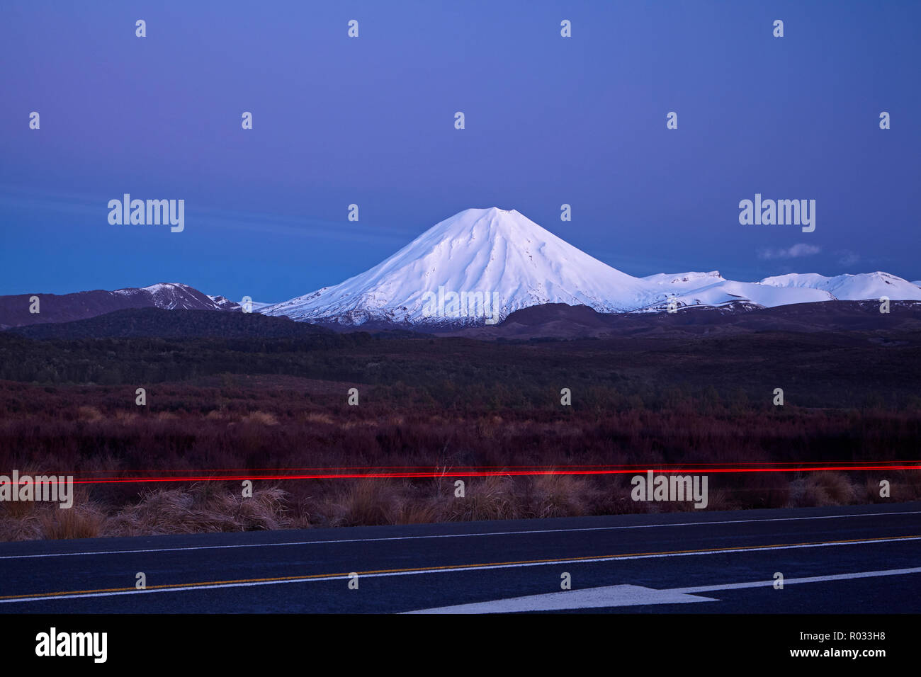Mt Ngauruhoe at dawn, and tail lights on Desert Road, Tongariro National Park, Central Plateau, North Island, New Zealand Stock Photo