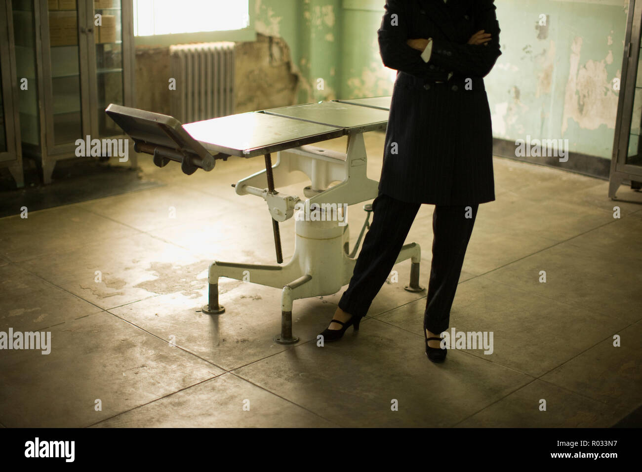 Folded arms of a mid-adult business woman standing beside an old operating table in a derelict building. - Stock Image