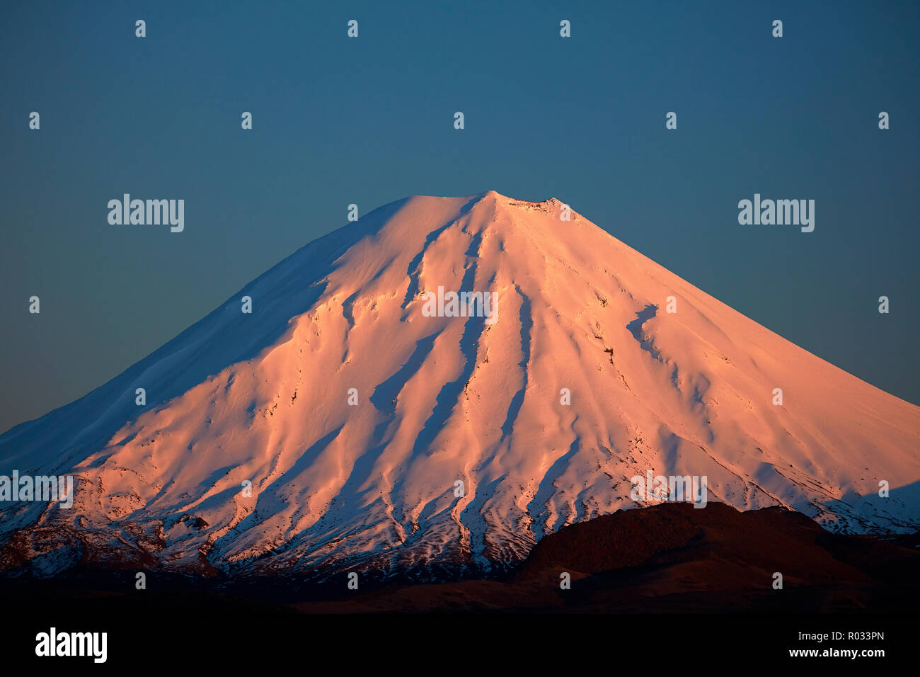 Alpenglow on Mt Ngauruhoe at dawn, Tongariro National Park, Central Plateau, North Island, New Zealand - Stock Image