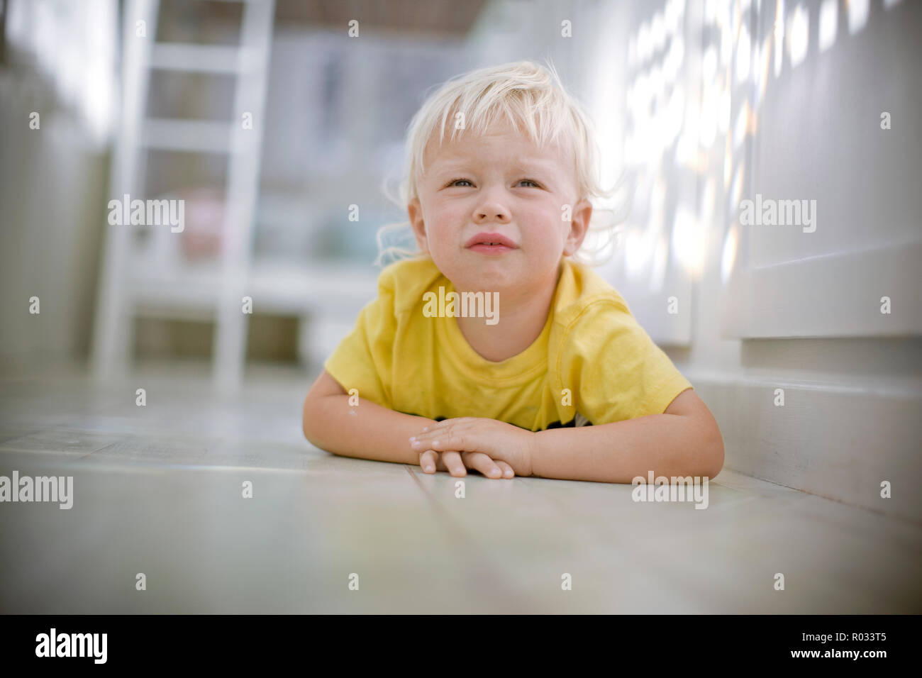 Upset young boy lying on his stomach on the floor - Stock Image