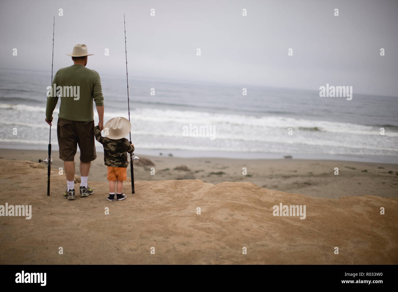 f56e98eac4f Young boy and his father walking along a beach carrying fishing rods and  wearing hats.