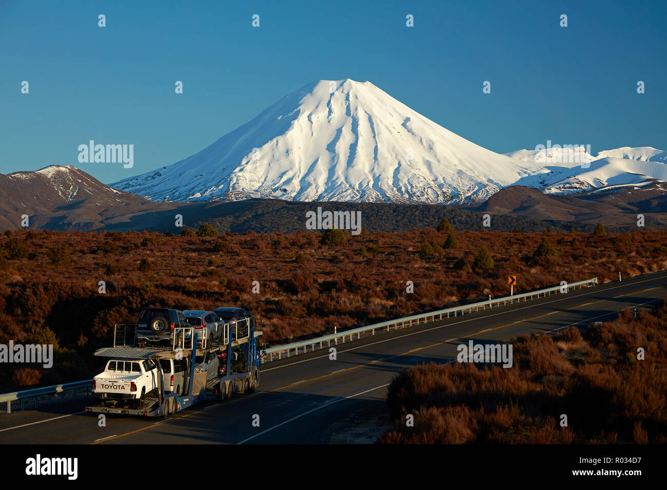 Mt Ngauruhoe and car transporter on Desert Road, Tongariro National Park, Central Plateau, North Island, New Zealand - Stock Image