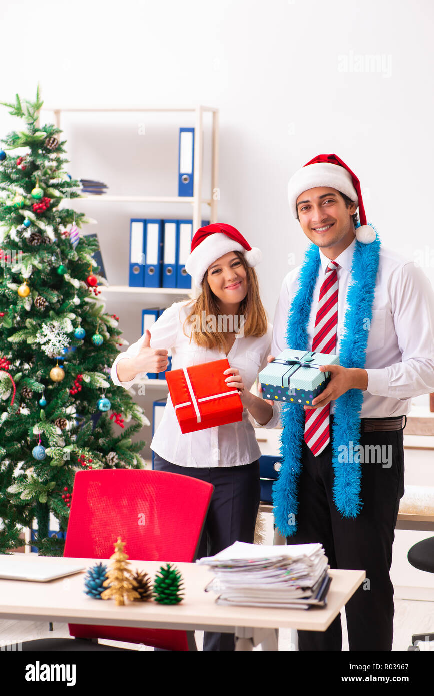 Colleagues exchaing christmas presents in office Stock Photo ...