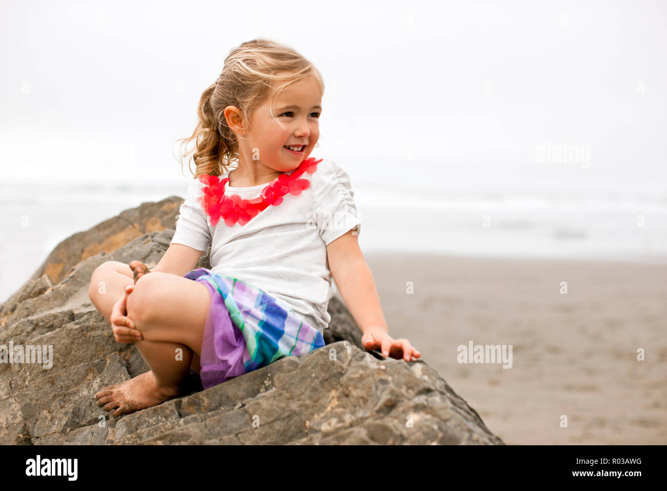 Smiling young girl sitting on a rock on a beach. Stock Photo