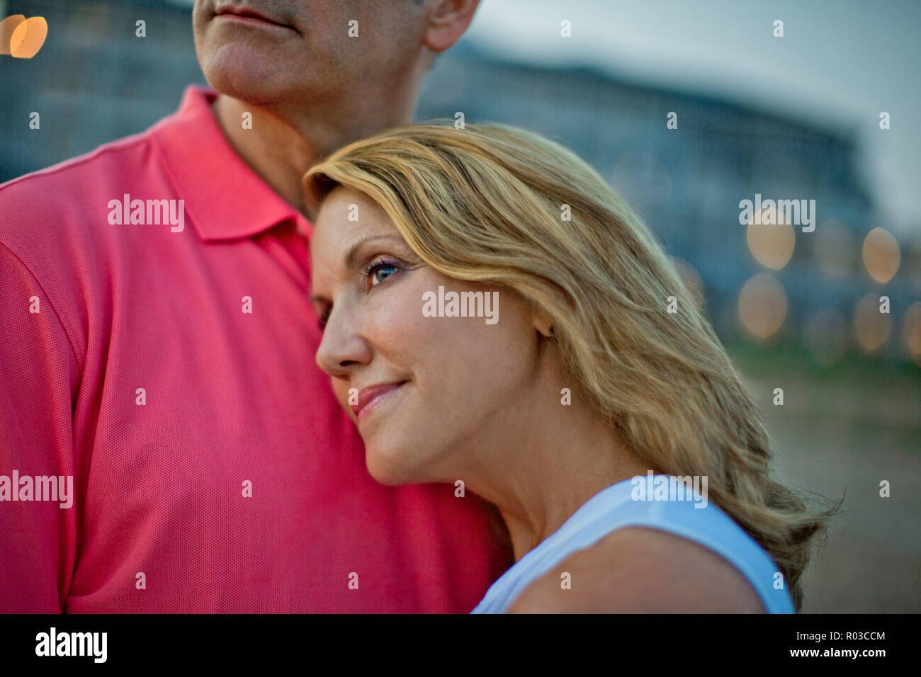 Woman lovingly resting her head on her husband's chest as they watch the sunset at the beach. - Stock Image