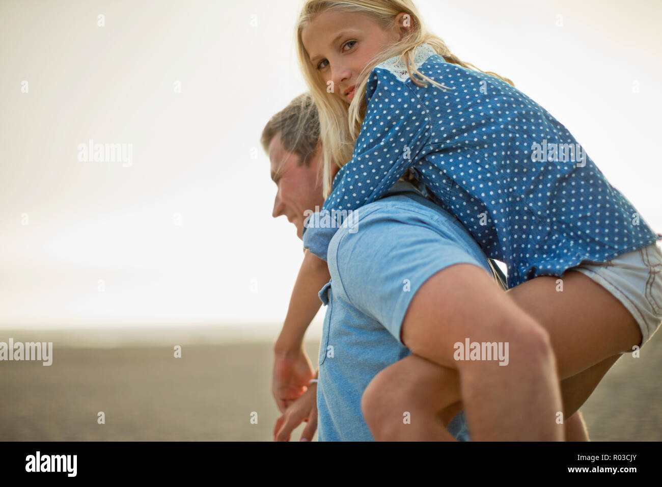 Portrait of a happy young girl being carried on her father's back. - Stock Image
